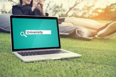 Searching University Background Concept on laptop screen. With Asian young woman sitting on bean bag and using smartphone, tablet, cell phone at outdoor garden royalty free stock image