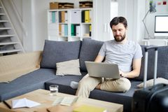 Searching for vacation offers. Young casual man with laptop sitting on sofa and searching for online travel offers before vacation royalty free stock photo