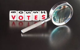 Searching for votes. Text ' votes ' in red uppercase letters on small white cubes placed beside a hand magnifier, black background Royalty Free Stock Photography
