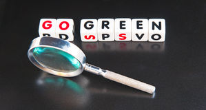 Searching for ways to go green. Text ' go green ' in upper case letters on white cubes with hand magnifier, dark background Stock Photos