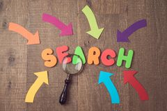 Searching website and content by SEO ranking concep. T. Letters, magnifying glass and arrows over wooden background. View from above Royalty Free Stock Photography