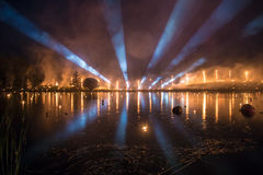 Searchlight show with fire show over a lake at night. Leigo Lake Music festival 2016 Royalty Free Stock Photos