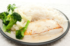 Seared halibut fillet with cream. Pan seared halibut fillet with cream and lemon glaze, served with lemon rice and fresh vegetables Royalty Free Stock Image