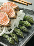 Seared Salmon Sashimi Black Pepper with a Mouli an. Plate of Seared Salmon Sashimi coated in Black Pepper with a Mouli and Asparagus Salad royalty free stock image