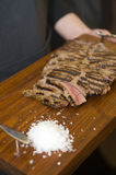 Seared sirloin. Delicious freshly prepared seared sirloin on a wooden cutting board, sliced and ready to serve with a small pile of salt flakes on the side Royalty Free Stock Photography