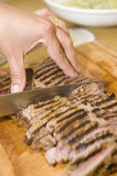 Seared sirloin. Delicious freshly prepared seared sirloin on a wooden cutting board, in the process of being cut by the chef Stock Image