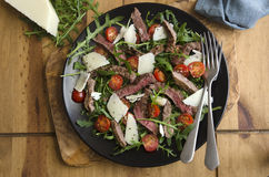 Seared steak salad. Seared steak, rocket and tomato salad topped with shaved Parmesan Stock Photos