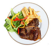 Seared T-bone steak meal from above. View from above of a meal of T-bone steak, salad and french fries royalty free stock photo