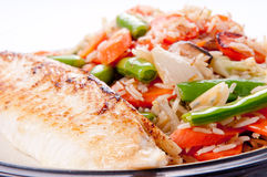 Seared tilapia fish filet with rice stir fry Royalty Free Stock Image