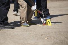 Searh del equipo y marcador forenses de las pruebas en el entrenamiento de la escena del crimen imagen de archivo