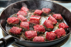 Searing beef cubes Stock Images