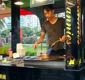 Searing Steak Pieces with a Blowtorch. KAOHSIUNG, TAIWAN -- JUNE 9, 2016: A young male chef sears pieces of steak with a blowtorch at an outdoor food stall Royalty Free Stock Photos