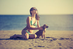 Молодая женщина играя с любимчиком собаки на пляже во время восхода солнца или захода солнца Девушка и собака имея потеху на seas Стоковое Изображение RF