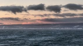 Stormy seas with mountains. Seas with mountains in background stock photography