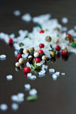 Seasalt. Seasalt, thyme and colorful peppercorns on a shiny black Royalty Free Stock Photography