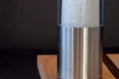 Seasalt grinder,on black background,selective focus,. Seasalt grinder on a cutting board, selective focus,voluntary blur Royalty Free Stock Image