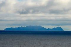 Seascape με το νησί, το μπλε ουρανό και τα σύννεφα στοκ εικόνες