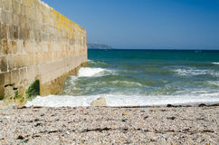 Seascape μπλε ουρανός λιμενικών τοίχων παραλιών χαλικιών στοκ φωτογραφία με δικαίωμα ελεύθερης χρήσης