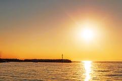 Seascape στο ηλιοβασίλεμα, φάρος στο υπόβαθρο ακτών Στοκ Εικόνα