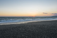 seascape χαλικιών παραλιών ηλιοβασίλεμα θάλασσα θυελλώδης Στοκ Εικόνα