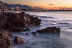 Seascape захода солнца долгой выдержки трясет ровную воду Стоковое Фото