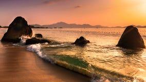Seascape природы с валунами на песчаном пляже и вздымаясь волнами на восходе солнца стоковая фотография rf