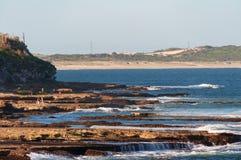 Seascape с живописными горными породами и песчаный пляж на предпосылке стоковое изображение