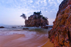 Seascape. Rocks at the beach in Malaysia with slow waves Royalty Free Stock Images