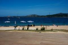 Seascape av Cannigione med strandparaplyer Arkivbild