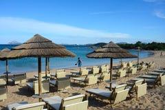 Seascape av en sandig strand av Liscia Ruja med strandparaplyer Royaltyfri Foto