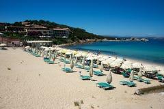 Seascape av en sandig strand med solstolar och strandparaplyer Arkivbild