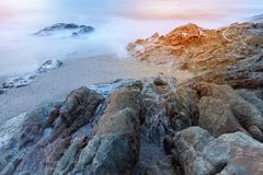 Seascape av vaggar i lång exponering, sammansättning av naturen för baksida Arkivfoto