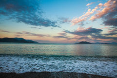 Seascape on background of mountains and sky clouds at dawn Royalty Free Stock Images