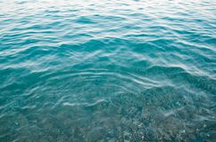 Astract sea background, ripple surface of turquiose water. Seascape background, ripple surface of transparent water, view of colorful stones bottom underwater stock photography