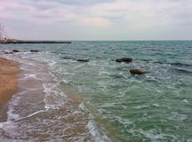 Seascape in bad weather. Sand beach, rocks, waves and pier Stock Photos