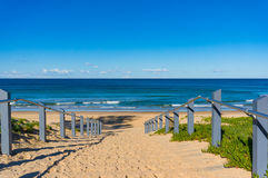 Seascape of beach entrance with wooden rails and sand shore Stock Images