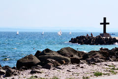Seascape. Beach with memorial cross and beautiful sailboats Royalty Free Stock Photo