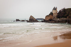 Seascape Biarritz France. Rocky coastal seascape in Biarrtiz, France on the Atlantic ocean. Surfers in the water surfing green waves towards a sandy beach stock photography