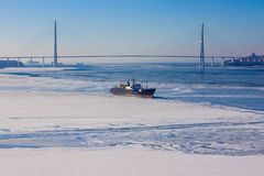 Cold sea, covered with ice. Seascape in blue tones. On the water a small ship, the sea partially frozen, covered with white snow. In the distance a huge cable Royalty Free Stock Images