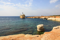 Seascape: boat EDRO III shipwrecked near the rocky shore at the sunset. Mediterranean, near Paphos. Cyprus Royalty Free Stock Photography
