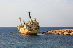 Seascape: boat EDRO III shipwrecked near the rocky shore at the sunset. Mediterranean, near Paphos. Cyprus Royalty Free Stock Image