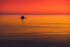 Seascape with boat. And fishermen intense vivid red orange royalty free stock photography