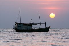 Seascape with boat and sunset Stock Images