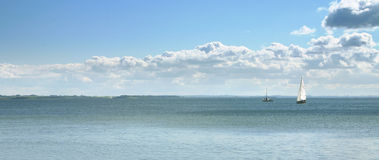 Seascape with boats. Seascape with boat with white sail against blue water and sky stock photos