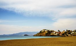 A seascape from Bolnuevo,Murcia,Spain. A seascape of a sandy beach and houses on the distant cliffs under wispy clouds from Bolnuevo,Murcia,Spain royalty free stock image
