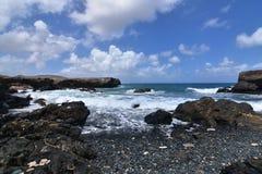 Seascape bonito do preto Pebble Beach do ` s de Aruba em Aruba imagem de stock
