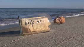 """Seascape with bottle with message """"help me"""" in sand. Seascape with transparent bottle with a message """"help me"""" in the beach sand"""