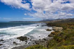 Seascape on California Central Coast under Blue Sky with Spring Flowers. Colorful coastal landscape with spring flowers under blue sky and clouds on California royalty free stock image