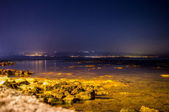 Seascape with city lights Stock Photography