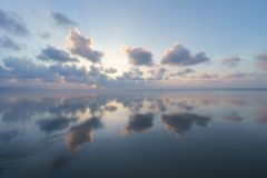 Seascape with clouds reflections. On beach royalty free stock images